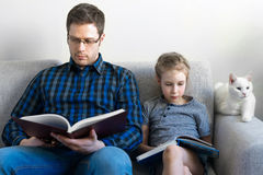 Father and his daughter reading books. Royalty Free Stock Photos