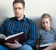 Father and his daughter reading books. Royalty Free Stock Images