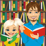 Father and his daughter reading interesting books in library Royalty Free Stock Image