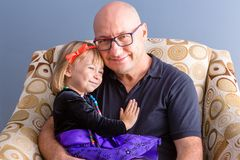 Father and his daughter sitting in armchair. Adult bold men in glasses, father with his happy daughter kid in holiday dressing, sitting in armchair and looking royalty free stock images