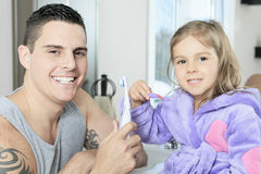 Father with his daughter to clean teeth in Royalty Free Stock Images