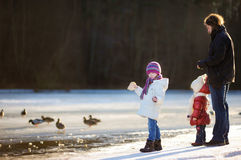 Father and his daughters feeding ducks at winter Stock Photo