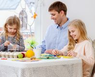 Father and his daughters painting and decorating easter eggs. Cheerful father and his daughters painting and decorating easter eggs Royalty Free Stock Photo