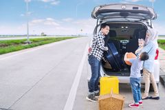 Father with his family ready for road trip. Image of young father with his family preparing suitcase into a car for a road trip. Shot on the roadside Royalty Free Stock Photos