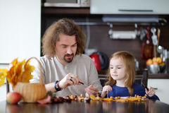 Father and his kid making chestnuts creatures Stock Photos