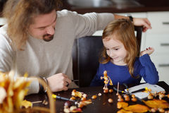 Father and his kid making chestnuts creatures Royalty Free Stock Images