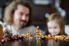 Father and his kid making chestnuts creatures. Together royalty free stock photography