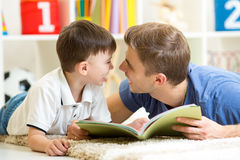 Father and his kid son read a book on floor at home Stock Photo