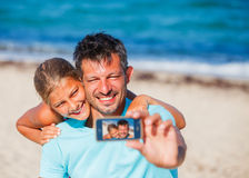 Father and his kids at beach taking selfie Stock Photo