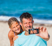 Father and his kids at beach taking selfie Royalty Free Stock Images