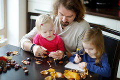 Father and his kids making chestnuts creatures Royalty Free Stock Image