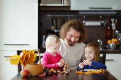 Father and his kids making chestnuts creatures. Together stock photos