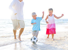 Father and his kids playing football together Stock Photo