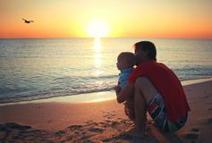 Father and his little baby son sitting on sunset beach. Family v Royalty Free Stock Photo