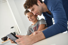 Father and his little boy enjoying playing on tablet Stock Images