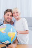Father and his little boy looking at globe Royalty Free Stock Photography