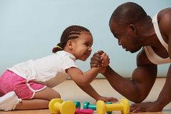Father and his little daughter arm wrestling on the floor at home. Handsome black young father is arm wrestling with his cute little daughter on the floor at royalty free stock photos