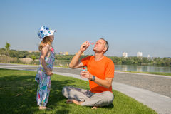 Father and his little daughter intently inflate soap bubbles Royalty Free Stock Image