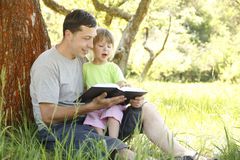 Father with his little daughter reads the Bible Stock Photography