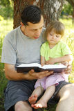 Father with his little daughter reads the Bible Stock Photo