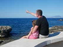 Father with his little daughter sitting on a sea coast royalty free stock image