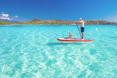 Father with his little happy son having fun on stand up paddle board. On Corsica island, France Stock Images