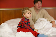 Father and his little son on the bed at hotel on vacation. Stock Images