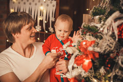 Father with his Little son decorating christmas tree with toys a. Nd flowers. Family preparing home for xmas celebration stock image