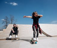 Father and his little son dressed in the casual clothes ride skateboards and have fun in a skate park with slides stock photos