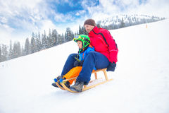 Father and his little son enjoying a sledge ride in famous ski r Royalty Free Stock Photos