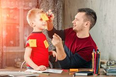 The father and his little son fool around doing homework for the school. stock photography