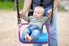 Father and his little son having fan on a swing. At summer day Royalty Free Stock Images