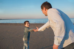 Father and his little son hold their hands on a beach in the evening Royalty Free Stock Photo