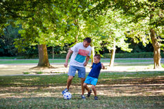 Father and his little son play soccer in park Stock Photos