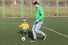 Father with his little son playing football, soccer in the park Royalty Free Stock Image