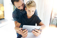 Father and his little son playing together on mobile computer, resting indoor.Bearded man with young boy using tablet PC in sunny Stock Photo