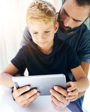 Father and his little son playing together on mobile computer, resting indoor.Bearded man with young boy using tablet PC in sunny Stock Images