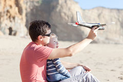 Playing with a toy plane. Father and his little son playing with toy plane together Royalty Free Stock Image