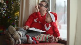 Father with his little son reading a book in cozy living room. Family time on holidays. Christmas morning near Christmas tree stock video footage
