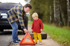 Father and his little son repairing car and changing wheel together on summer day stock photo