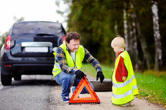 Father and his little son repairing car and changing wheel together on summer day Stock Image