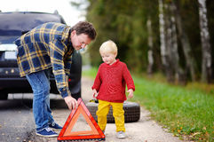 Father and his little son repairing car and changing wheel together on summer day Royalty Free Stock Photos