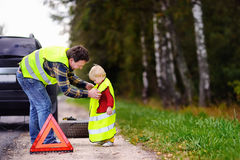 Father and his little son repairing car and changing wheel together on summer day Stock Images