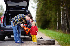 Father and his little son repairing car and changing wheel together on summer day Royalty Free Stock Images
