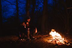 Father and his little son sitting together on the logs in front of a fire at the night. The hike in the forest. royalty free stock image
