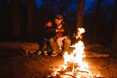 Father and his little son sitting together on the logs in front of a fire at the night. The hike in the forest. stock photography