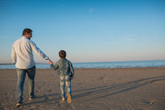 Father and his little son walk on a beach in the evening. Back view stock photography