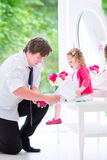 Father with his little toddler girl putting on her. Young happy father in a business suit and tie with cute little curly toddler girl, sitting on a white dresser Stock Photography