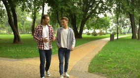Father in his 40s walking with son in park, sharing his life experience and tips. Stock footage stock video footage