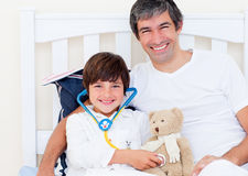 Father and his sick son playing with a stethoscope Royalty Free Stock Photo